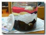 シソを容器に入れ、氷砂糖とレモン、焼酎を注ぐ